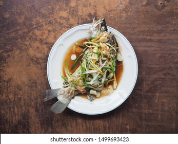 Top view steamed sea bass in soy sauce on wooden background