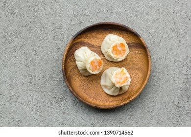 Top view of steamed shrimp shumai on a wood plate against grey cement background. Simplicity asian breakfast concept.
