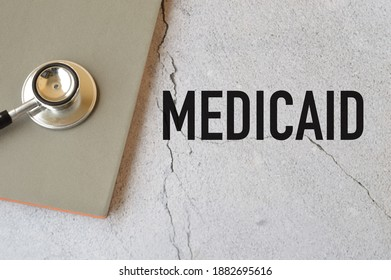 Top view of stethoscope and notebook over grey background written with MEDICAID.Medicaid in the United States is a federal and state program that helps with medical costs for some people
