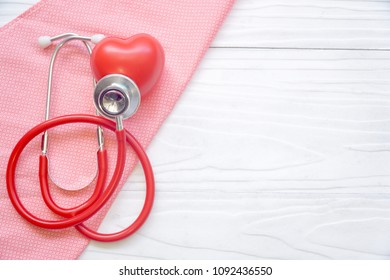 Top view of Stethoscope and red heart on pink fabric. White wood background. Health care / Medical concept. Copy space. Can be use for brochure, advertising, banner.