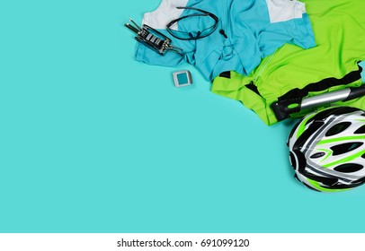 Top view of a still life of cycling sportive objects placed on teal color background with a text space