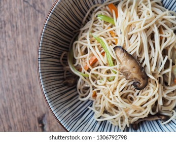 Top view of stir-fried Chinese noodles with vegetable in bowl on wooden table.