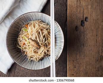 Top view of stir-fried noodles with vegetables on wooden table.