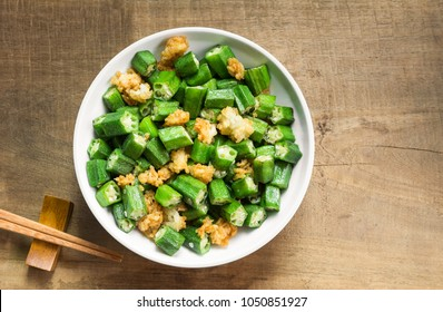 top view of stir-fried okra with salt in a ceramic dish on wooden table. homemade style healthy food concept.
