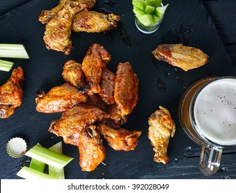 Top view of stone with crispy delicious buffalo chicken wings with hot spicy sauce. Black wood background with celery sticks and beer on it