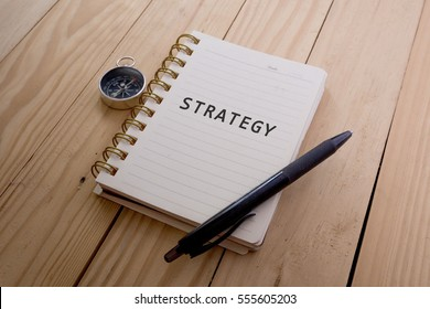 Top view of STRATEGY written on the notebook,travel planning concept.note book,compass,passport,film camera on the wooden desk.