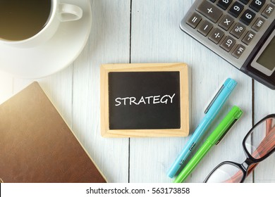 top view of STRATEGY written on the chalkboard,business concept.chalkboard,notebook,calculator,pen,glasses,coffee on the wooden desk.