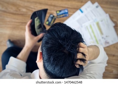 Top view of stressed young Asian man holding wallet with money and thinking about  finding money to pay credit card debt and all bills. He is holding head by another hand. Financial problem concept.