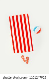 top view of striped beach towel, flip flops and inflatable beach ball isolated on white