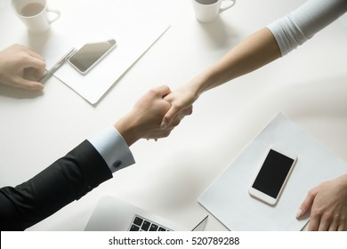Top view of a strong handshake between man and woman, both sides viewpoints and interests have been considered. Effective negotiation with client. Business concept photo. Horizontal