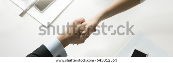 Top view of a strong handshake between man and woman, both sides viewpoints and interests considered. Business concept photo. Horizontal photo banner for website header design with copy space for text
