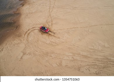 Top view of the stuck car on the sandy beach. Aerial photo of landscape