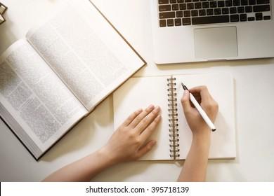 Top-Ansicht der Schüler Hand schreiben ein Buch mit Laptop in der Bibliothek Vintage-Ton.