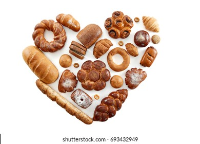 Top view studio shot of a heart shaped collection of different delicious freshly baked loafs of bread isolated on white food love nutrition healthy concept.