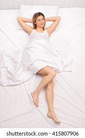 Top view studio shot of a young woman laying in bed covered with a white blanket and daydreaming