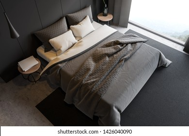 Top view of stylish master bedroom with gray walls, concrete floor, double bed on gray carpet, two bedside tables with books and plant and large window with mountain view. 3d rendering