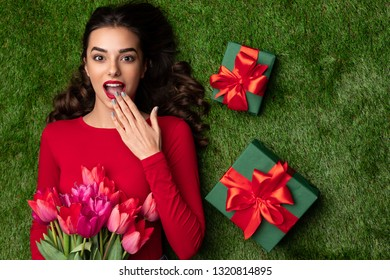 Top view of stylish woman with red lips covering mouth in surprise while lying on lawn with presents and flowers. Women day concept