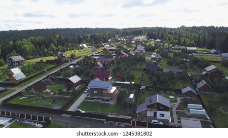 Top view of suburban areas with cottages in forest. Clip. Quiet and moderate life in forest terrain
