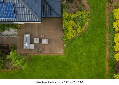 Draufsicht auf Vorstadthaus mit grünem Garten und Holzterrasse