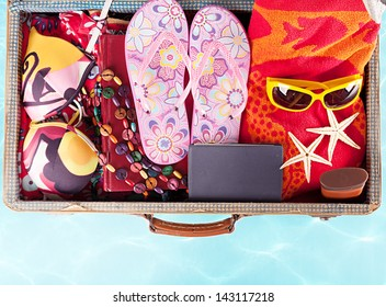 top view of a suitcase with full of summer stuff on blue background