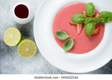 Top view of summer soup with fresh strawberries served in a white plate, closeup