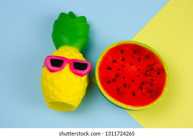 46d5f9c3af9 top view summer vibrant blue and yellow background with funny pineapple toy  in sunglasses and squishy