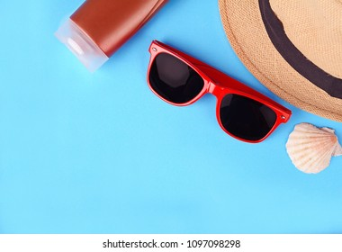Top view of sunglasses, shells, starfish, sunblock and hat with copyspace. Summer concept. Light blue background