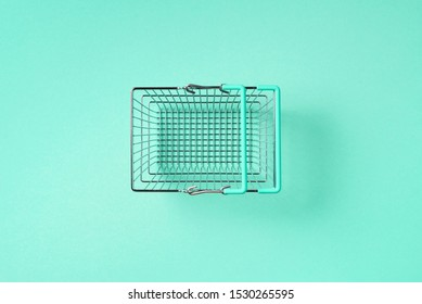 Top view of supermarket shopping basket on trendy green background. Black friday sale concept. Copy space. Sustainable lifestyle