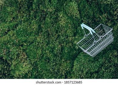 Draufsicht auf Supermarkt-Warenkorb auf grünem Gras, Mooshintergrund. Minimalismus. Black Friday Verkauf, Discount, Shopaholismus, Ökologie Konzept. Nachhaltiger Lebensstil, bewusster Konsum.