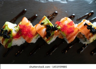 Top View of Sushi Roll with Salmon and Avocado on Top in Dark Tone / Japanese Food
