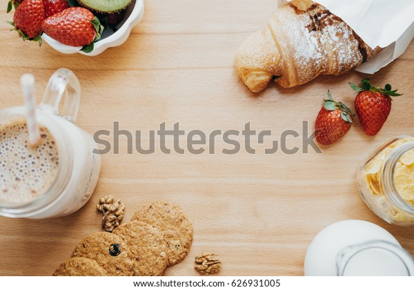 Top view of sweet breakfast with Coffee, milk, cookies, croissant, strawberry, kiwi on a wooden table