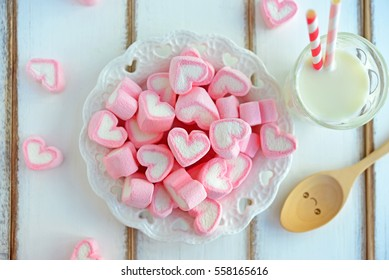Top view of sweet marshmallow in the shape of heart on white plate. Decorated with happy fork and glass of milk on wooden background. Concept about love and relationship. (Flat Lay for designed work)