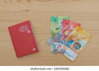 Top view of a Swiss Passport and swiss currency on a wooden table