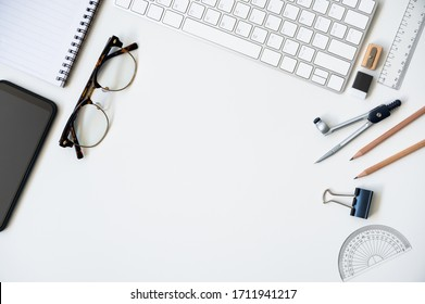 Top view table desk of office architect pencil, compasses tool, ruler, rubber, protractor grid, sharpener, glasses, smartphone, keyboard with copy space background.