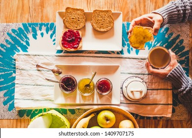 Top view of table full of food and beverage for breakfast morning time activit - fruit and coffee for healthy natural lifestyle people - woman eating bread with marmalade and drink cappuccino