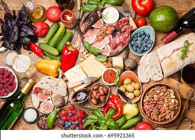 Top view table full of food. Italian antipasti wine snacks set. Cheese variety, nuts, Mediterranean olives, sauces, Prosciutto di Parma or jamon, tomatoes, vegatables and berries and wine.