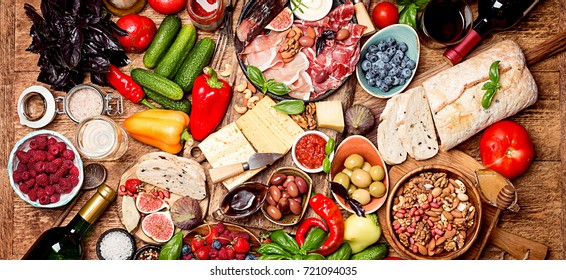 Top view table full of food. Italian antipasti wine snacks set. Cheese variety, nuts, Mediterranean olives, sauces, Prosciutto di Parma or jamon, tomatoes, vegatables and berries and wine
