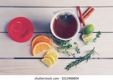Top view of table with herb tea with orange, lime and lemon in take away cup