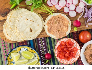 Top view of table with ingredients for vegetarian corn tacos -   refried beans, corn tortilla, radish, cut tomatoes.