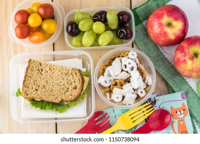 Top view of table with school lunch in containers - cheese sandwich, grapes, munchy snack, tomatoes.