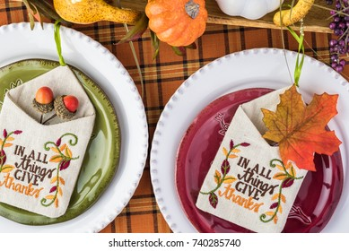 Top view of table set with colorful plates and center piece arrangement for Thanksgiving party.