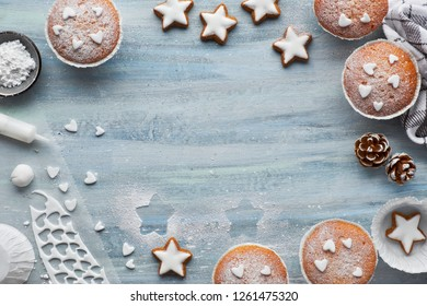 Top view of the table with sugar-sprinkled muffins, fondant icing and Christmas star cookies on blue wooden board with copy-space