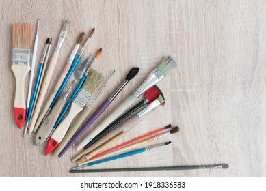 Top view of a table with a variety of artist brushes. There is room for text. Background, texture for a creative postcard