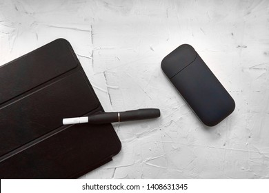 Top view of tablet and blue electronic cigarette with holder and stick. A few sticks are near tablet. Hybrid cigarette and black tablet lies on white decorative plaster background. Business concept.
