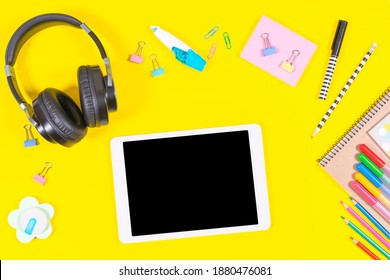 Top view to tablet computer, headphones and school supplies on yellow background. Online learning, education background