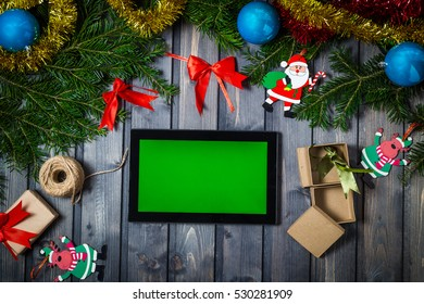 Top view with a tablet computer in the human hands on a wooden table. Near the table with tablet computer christmas bell, gift balls and fluffy fir branches. Closeup