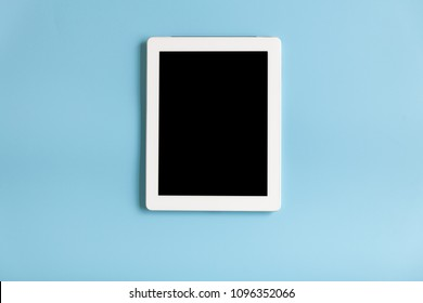 Top view of tablet on the blue pastel color background.