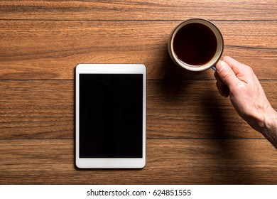 Top view of tablet on wood surface with coffee and hand