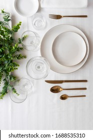 Top view of tableware with linen napkins, gold cutlery and white porcelain plates. Minimalist table settings background for dinner.
