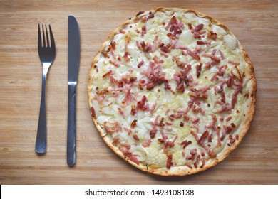 Top view of taditional food `Tarte Flambee` or `Flammkuchen` from German-French Alsace border region. The name means `pie baked in the flames`, similar to a thin pizza with bacon and soured cream